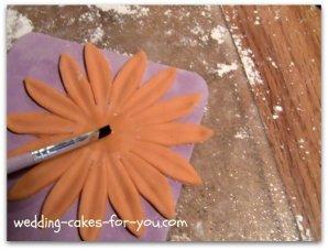 Brushing gum glue on the gumpaste Daisy