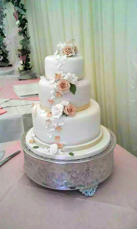 A beautiful fondant wedding cake with gumpaste Roses by Ottie's Cakery