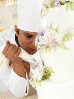 Pastry chef decorating a wedding cake