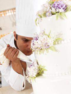 Chef Decorating A Wedding Cake