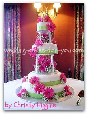 a beautiful fondant wedding cake with pink Gerbera daisies