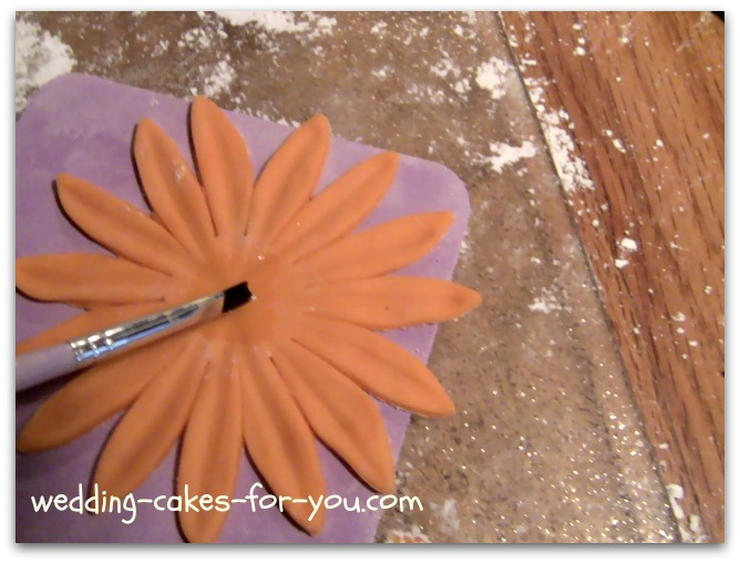 Brushing gum glue on the gumpaste Daisy