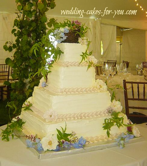 Square wedding cake with fresh flowers by Lorelie at a backyard celebration