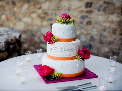 small wedding cake with orange ribbon and pink flowers