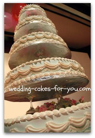 five tiered wedding cake with champagne glasses