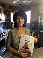 happy customer holding wedding cakes with Lorelie step by step book in print