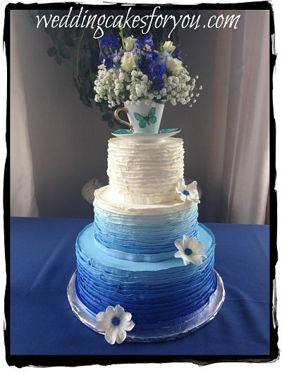 Blue ombre wedding cake with a tea cup and flower topper
