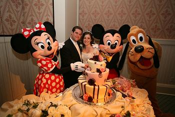 Bridal couple with a disney wedding cake