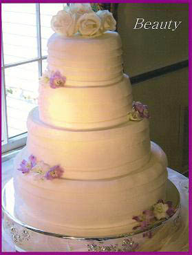 A fondant wedding cake made using strips of dfondant to mimic the brides dress