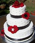 buttercream wedding cake and red flowers