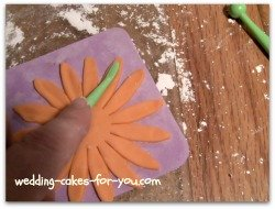 Using the veining tool to make an impression on the gumpaste Daisy petals