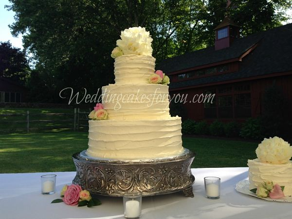rustic wedding cake with fresh flowers on a silver cake stand