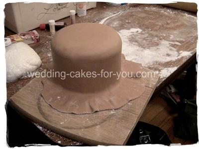 Cake being covered in fondant